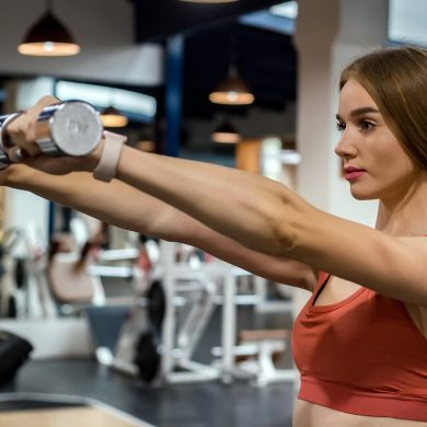 beautiful-young-woman-trains-deltoid-in-gym-BAVE37S.jpg