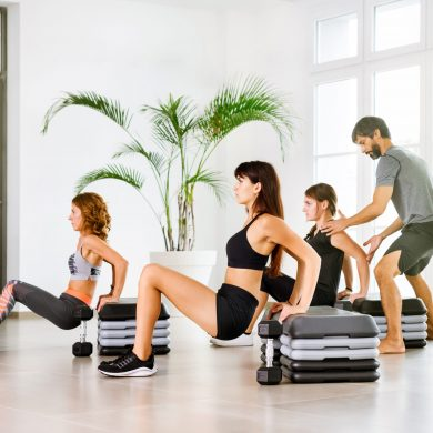Fitness class with young people doing push down exercise with a personal trainer assisting in a high key gym in a health and fitness or healthy lifestyle concept