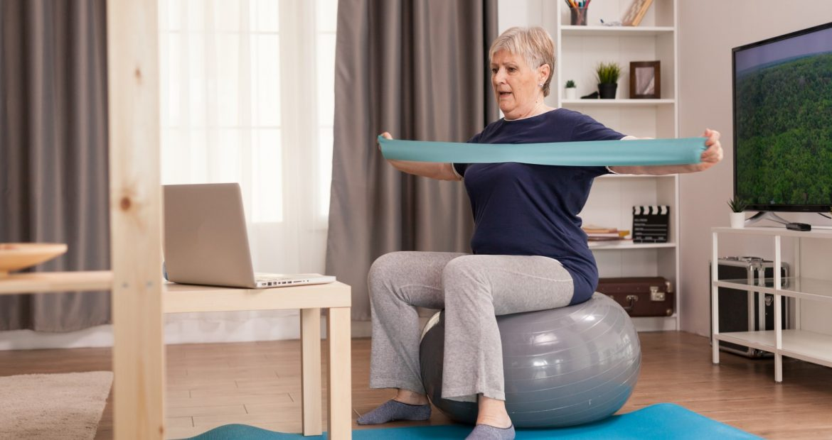 Elderly woman workout at home in front of the laptop. Old person pensioner online internet exercise training at home sport activity with dumbbell, resistance band, swiss ball at elderly retirement age